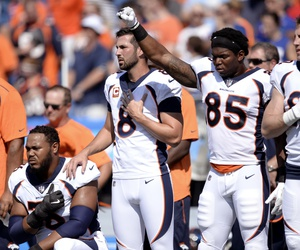 Denver Broncos tight end Virgil Green (85) gestures as teammate Max Garcia, left, takes a knee during the paying of the national anthem prior to an NFL football game against the Buffalo Bills, Sunday, Sept. 24, 2017, in Orchard Park, N.Y.