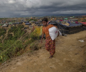 A Rohingya Muslim girl, who crossed over from Myanmar into Bangladesh, walks back to her shelter after collecting aid in Taiy Khali refugee camp, Bangladesh, Sept. 27, 2017.