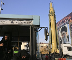A woman steps out a public bus next to a Ghadr-H missile and a portrait of the Supreme Leader Ayatollah Ali Khamenei on display for the annual Defense Week, marking the 37th anniversary of the 1980s Iran-Iraq war, at Baharestan Sq. in Tehran, Iran.