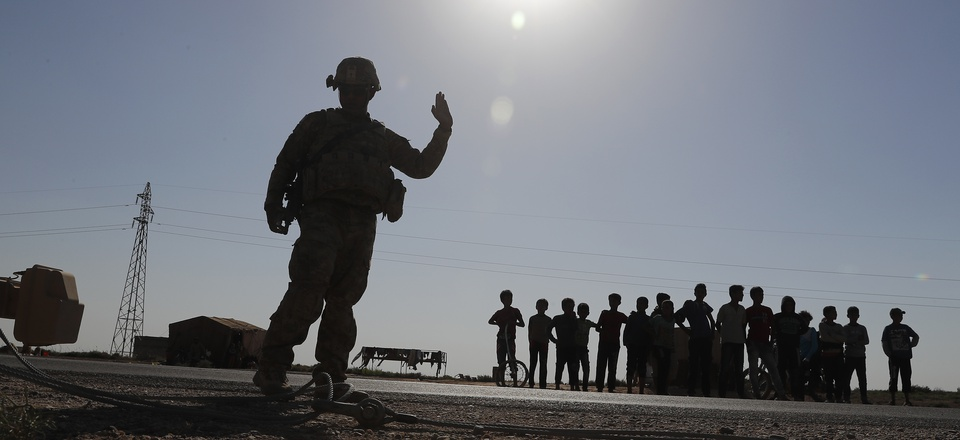 A U.S. silhouetted soldier, left, directs his armored convoy as Syrian children, background, watch, on a road that links to Raqqa city, northeast Syria, Wednesday, July 26, 2017.