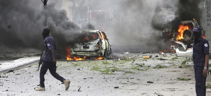 Somali soldiers pass burning vehicles outside Midnimo mall after a car bomb attack on a popular mall in Mogadishu earlier this summer.