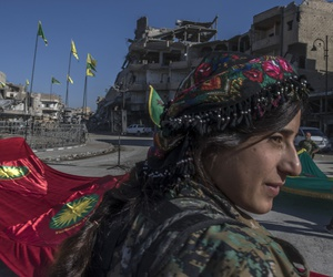In this Thursday, Oct. 19, 2017 photo, fighters from the Women's Protection Units, or YPJ, hold a celebration in Paradise Square in Raqqa, Syria.