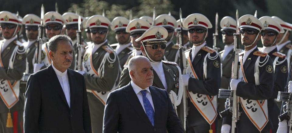 Iraqi Prime Minister Haider al-Abadi, center, reviews an honor guard while accompanied by Iranian Senior Vice-President Eshaq Jahangiri, at the Saadabad Palace in Tehran, Iran, Oct. 26, 2017.