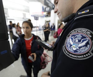 A U.S. Customs and Border Protection officer helps a passenger navigate one of the new facial recognition kiosks at George Bush Intercontinental Airport, in Houston, July 12, 2017.