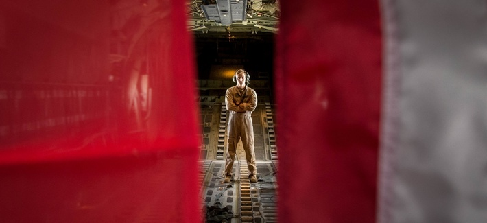 A U.S. Marineposes in between the U.S. Marine Corps flag and U.S. American flag in a KC-130J Super Hercules while forward deployed in the Middle East, Sept. 3, 2017.