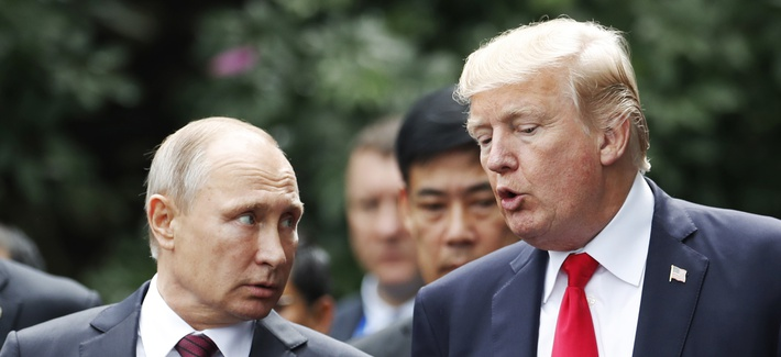U.S. President Donald Trump and Russia's President Vladimir Putin talk during the family photo session at the APEC Summit in Danang, Vietnam, Saturday, Nov. 11, 2017.