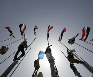 Supporters of Yemen's former President Ali Abdullah Saleh, who are allies of Shiite rebels known as Houthis, climb flag poles during a rally to mark the first anniversary of the Saudi-led military campaign against them, in Sanaa, Yemen, March 26, 2016.