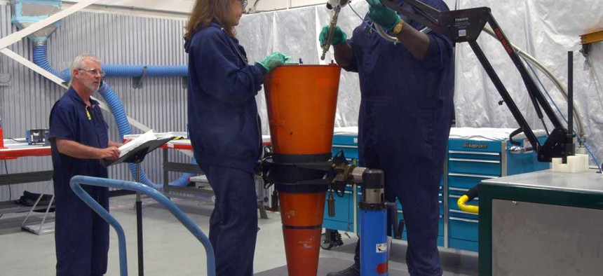 Two employees working on a W76 warhead