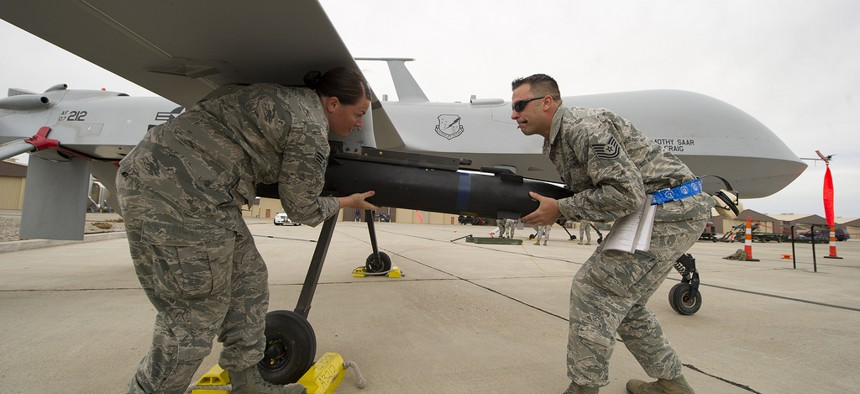 Two airmen load an inert missile onto an MQ-1 Predator drone during a competition at Holloman Air Force Base, N.M, on April 5, 2013.