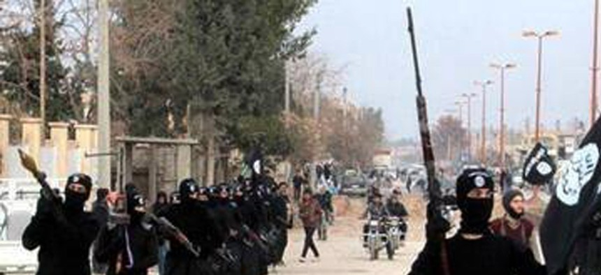 Fighters with the al-Qaeda linked ISIL march in Raqqa, Syria.