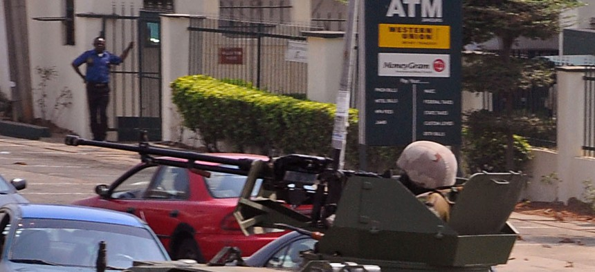 Nigerian soldiers patrol with a armored vehicle in the city of Abuja, Nigeria, Saturday, Feb. 7, 2015.