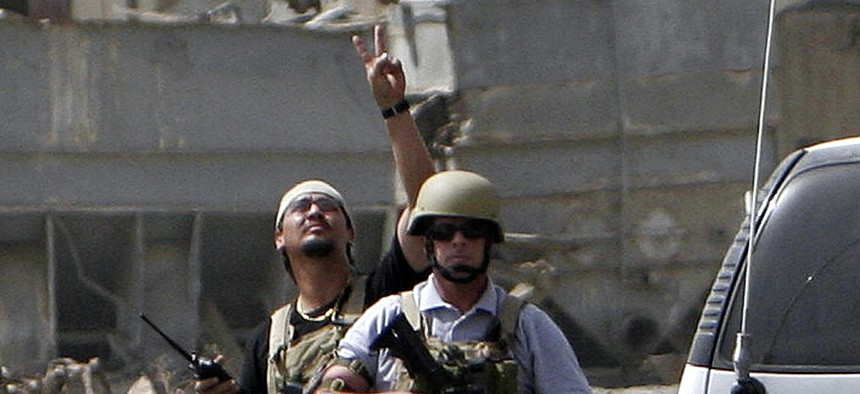 A private contractor gestures to his colleagues flying over in a helicopter as they secure the scene of a roadside bomb attack in Baghdad, Iraq, on July 5, 2005.