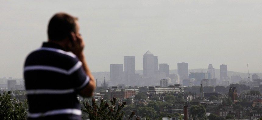A man talks on a mobile phone as the hi-rise buildings of the banks based in the Canary Wharf business district are seen in the distance from Parliament Hill on Hampstead Heath in London, Sept. 23, 2011.