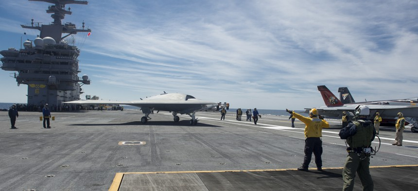 An X-47B Unmanned Combat Air System (UCAS) demonstrator taxies on the flight deck of the aircraft carrier USS George H.W. Bush (CVN 77).