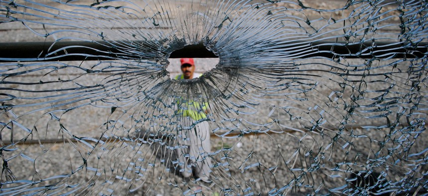 A Pakistani rescue worker is seen through the bullet-riddled window of a passenger train following an attack by unknown gunmen in the southwest Pakistani province of Balochistan, Aug. 28, 2011.