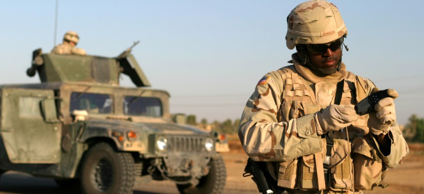 U.S. Army Staff Sgt. Lorenzo Johnson examines his Global Positioning System receiver during a route reconnaissance patrol of Alternate Supply Route Boston in Iraq.