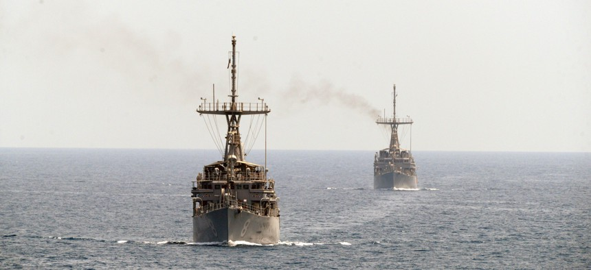 The mine countermeasure ships USS Scout (MCM 8), left, and USS Gladiator (MCM 11), transit the Strait of Hormuz.