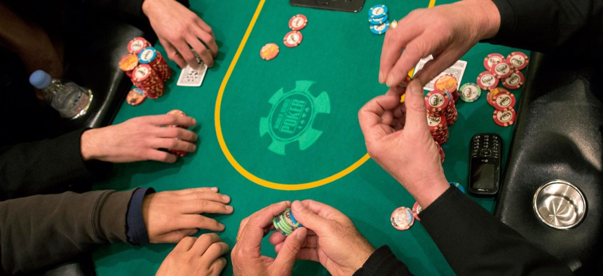 In this Feb. 27, 2013 photo, poker players cast their bets during a hand of Texas Hold 'em at the poker room at Caesar's Palace in Las Vegas.