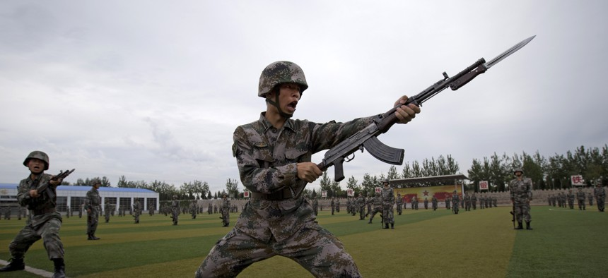 Chinese People's Liberation Army cadets take part in a bayonet drills at the PLA's Armoured Forces Engineering Academy Base, on the outskirt of Beijing, China Tuesday, July 22, 2014.