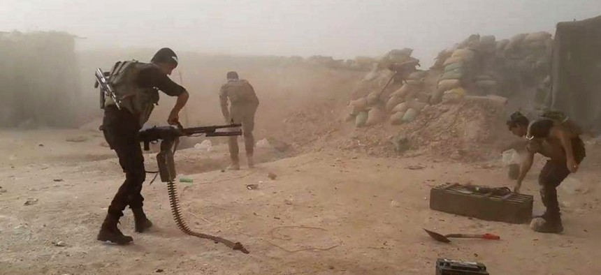 In this image taken Friday, May 29, 2015, Iraqi anti-terrorism forces battle with Islamic State group extremists as they defend their base against Islamic State group extremist attack outside Fallujah.
