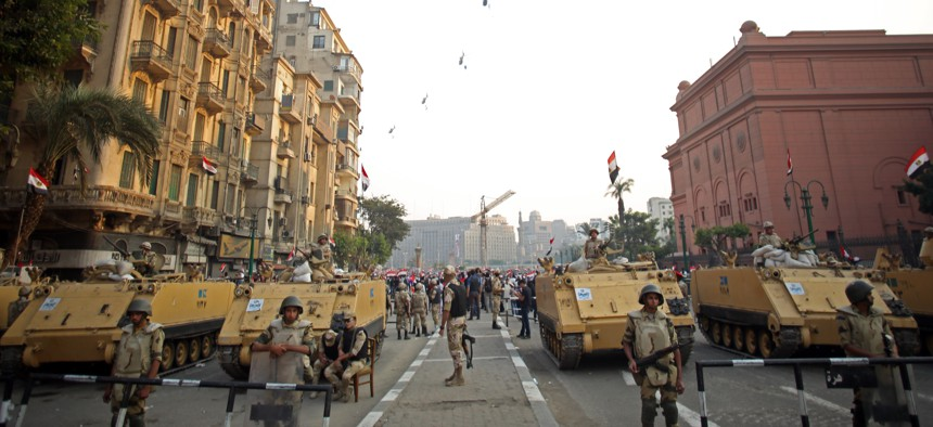 Egyptian military helicopters fly overhead as army soldiers stand guard at an entrance to Tahrir Square, in Cairo, Egypt., on October 6, 2013.
