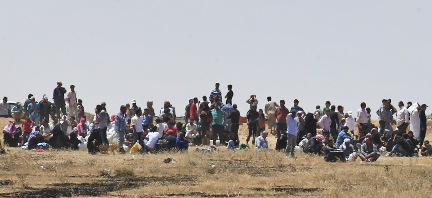 Syrian refugees wait on the Syrian side of the Syria-Turkey border in order to cross, Thursday, June 11, 2015.