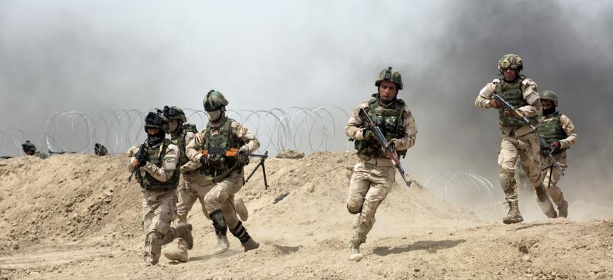 Iraqi soldiers run through a breach in a berm while training at Camp Taji, Iraq, on June 2, 2015.