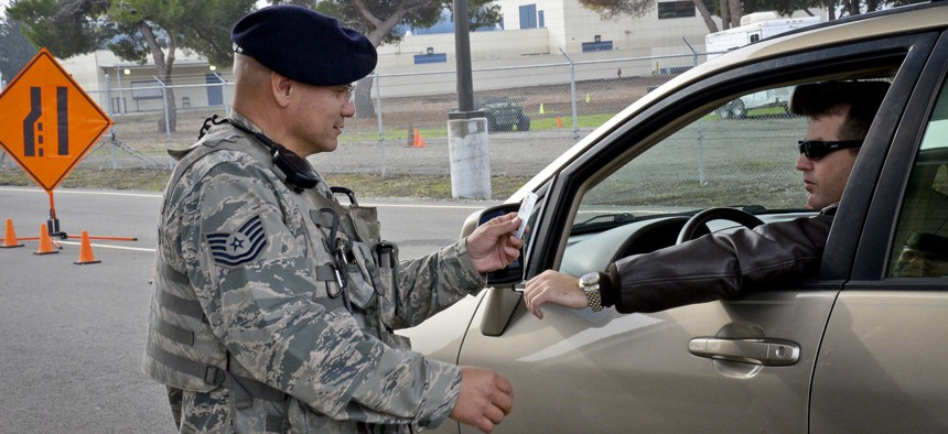 A California Air National Guard NCO checks an idenitification card at the main gate to Moffett Federal Airfield, Calif., on Dec. 8, 2014.