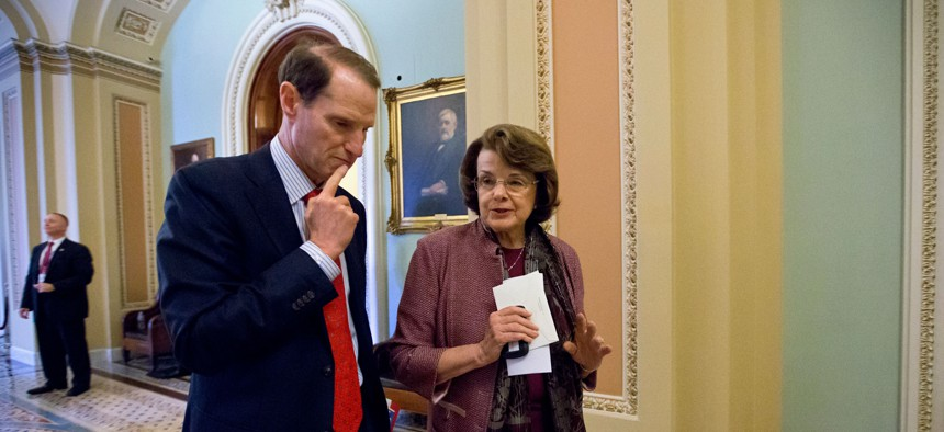 Sen. Ron Wyden, D-Ore., left, walks with Sen. Dianne Feinstein, D-Calif. on Capitol Hill in Washington, June 27, 2013.