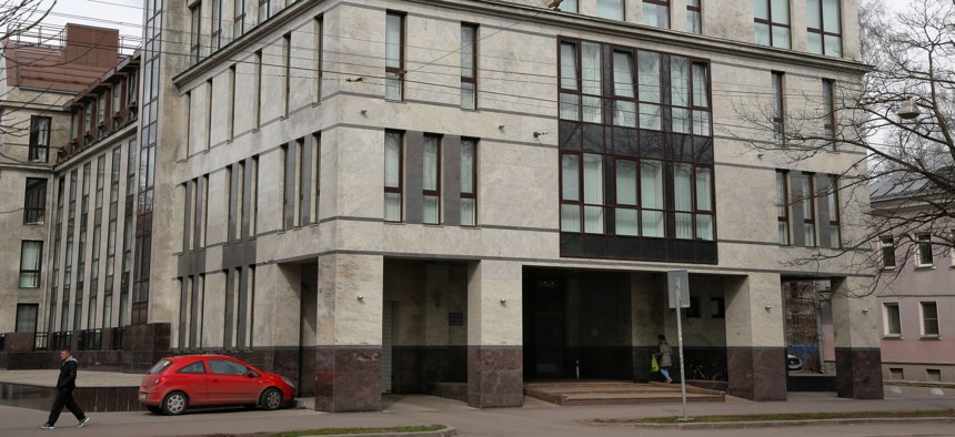 """In this picture taken on Sunday, April 19, 2015, a women enters the four-story building known as the """"troll factory"""" in St. Petersburg, Russia."""