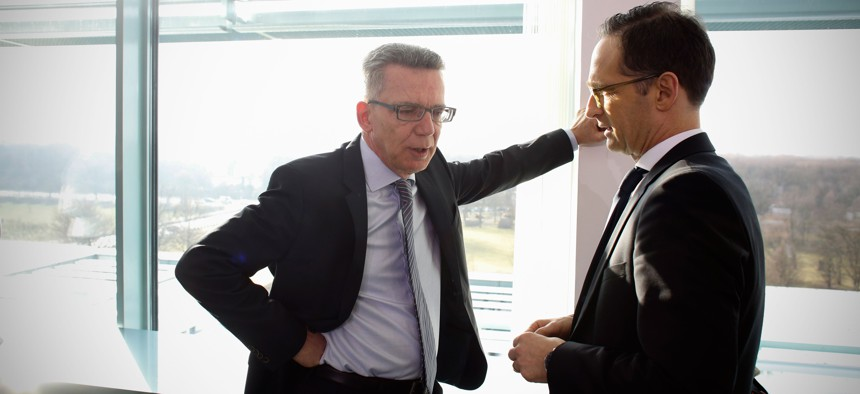 Interior Minister Thomas de Maiziere, left, talks to Justice Minister Heiko Maas prior to the cabinet meeting at the chancellery in Berlin, Germany, Wednesday, Feb. 25, 2015.
