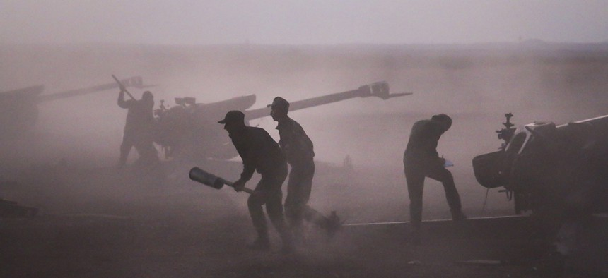 After launching new offensives under Russian air cover, Syrian army personnel load howitzers near the village of Morek in Syria, Oct. 7, 2015
