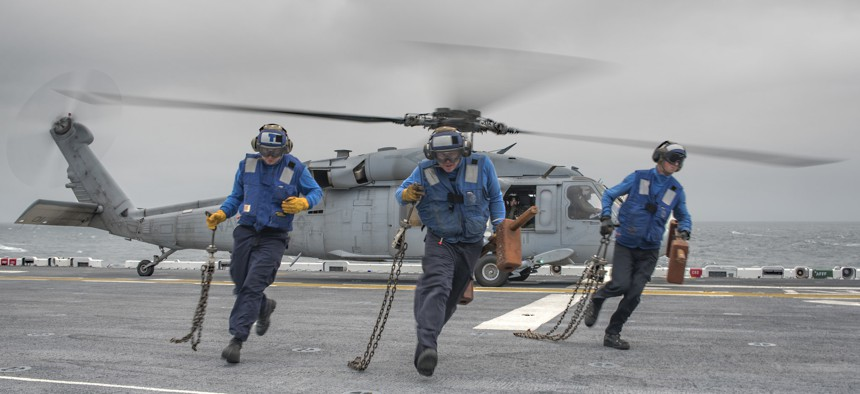 Three aviation boatswain's mates (handling) from the amphibious assault ship USS Wasp (LHD 1) and USS Bataan (LHD 5) conduct a chock and chain evolution with an SH-60 Sea Hawk aboard Wasp.