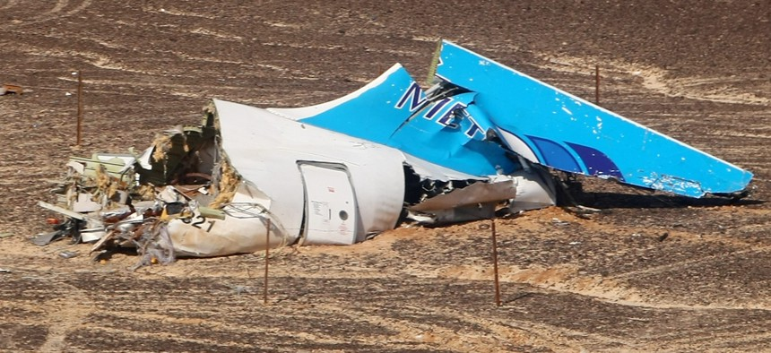 Egyptian Military on cars approach a plane's tail at the wreckage of a passenger jet bound for St. Petersburg in Russia that crashed in Hassana, Egypt, on Sunday, Nov. 1, 2015.