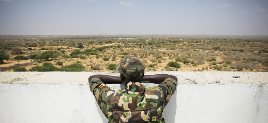 A Ugandan soldier serving with the African Union (A.U.) Mission in Somalia (AMISOM) looks over an open tract of land from the roof of Mogadishu University.