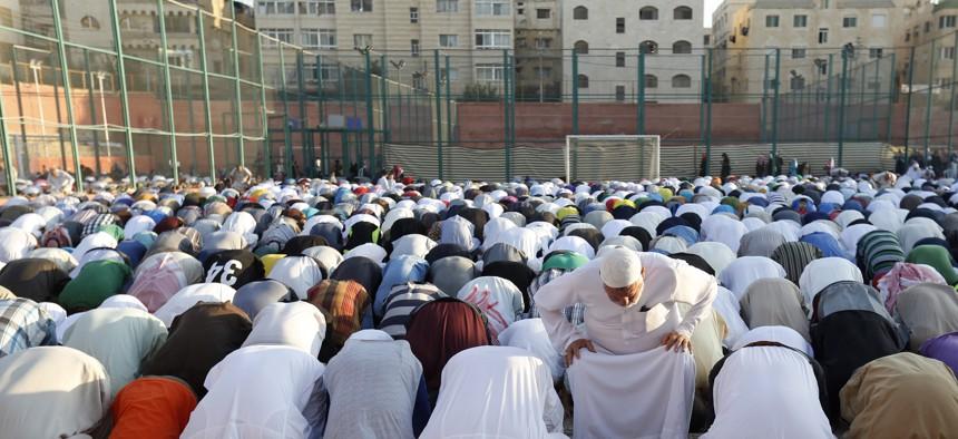 In this Friday, July 17, 2015 photo, worshippers attend the Eid al-Fitr prayers in an open field in Amman, Jordan.