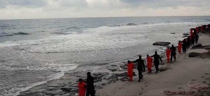 In this file image made from a video released Sunday, Feb. 15, 2015 by militants in Libya claiming loyalty to the Islamic State group purportedly shows Egyptian Coptic Christians in orange jumpsuits being led along a beach.
