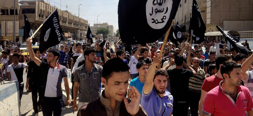 In this Monday, June 16, 2014 file photo, demonstrators chant pro-Islamic State group slogans as they wave the group's flags in front of the provincial government headquarters in Mosul.