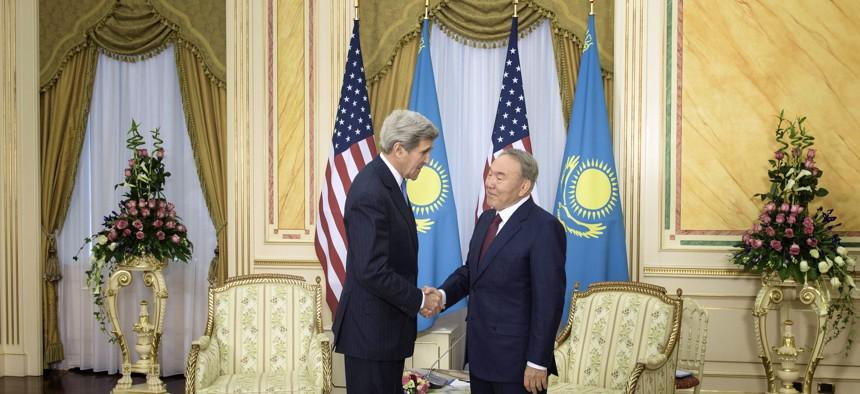 U.S. Secretary of State John Kerry, left, and Kazakhstan's President Nursultan Nazarbayev shake hands before a meeting at the Presidential Palace Monday, Nov. 2, 2015 in Astana, Kazakhstan.