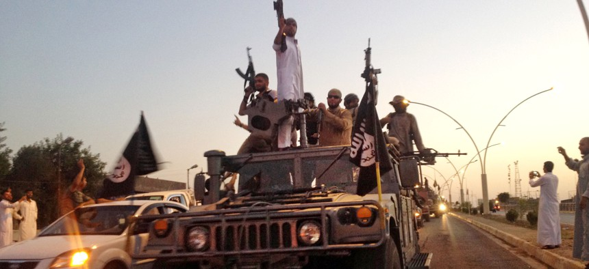 In this file photo taken Monday, June 23, 2014, militants from the Islamic State parade in a commandeered Iraqi security forces armored vehicle on a main street in Mosul, Iraq.
