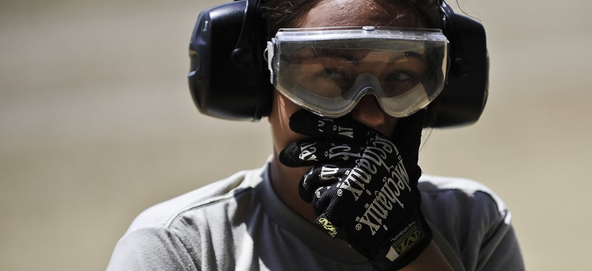 A U.S. airman working as a safety spotter covers her mouth from the exhaust fume of a C-130 Hercules cargo plane at Fort McCoy, Wis. July 22, 2013.