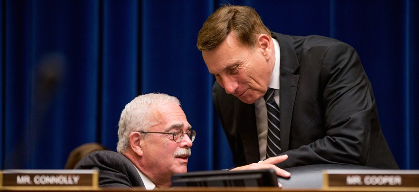 Rep. Gerald Connolly, D-Va., left, speaks with Rep. John Mica, R-Fla., right, on Capitol Hill in Washington, Wednesday, June 17, 2015, during the House Oversight and Government Reform Committee hearing.