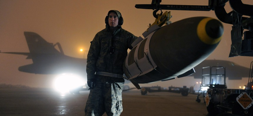 An Airman steadies a GBU-31 joint direct attack munition while preparing to load it on a B-1B Lancer on Ellsworth Air Force Base, S.D., March 27, 2011.