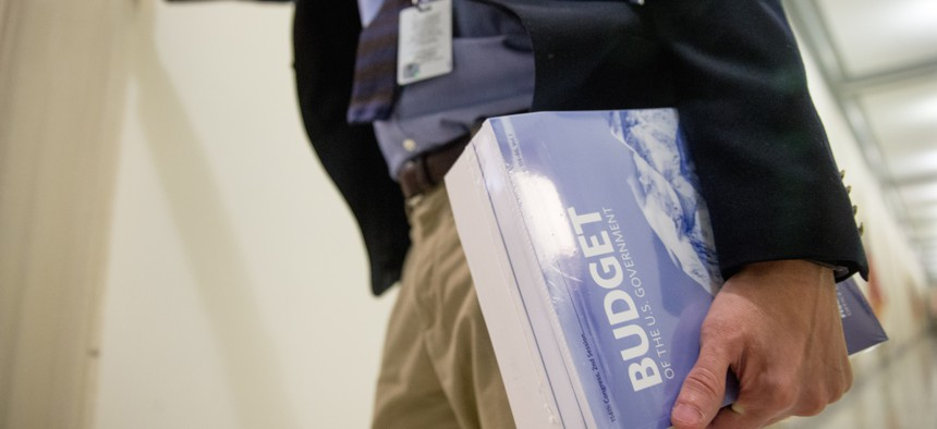 A Capitol Hill staff member holds a copy of President Barack Obama's fiscal 2017 federal budget after it is delivered to the House Budget Committee Room on Capitol Hill in Washington, Tuesday, Feb. 9, 2016.