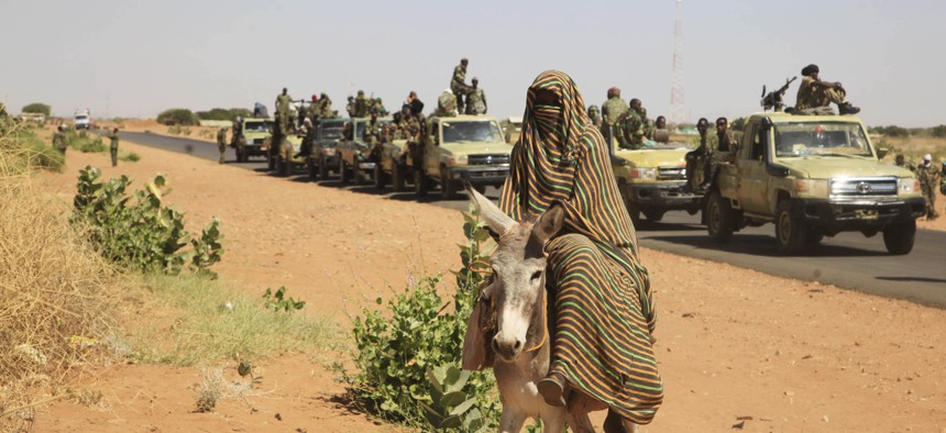 Nov. 20, 2014 photo taken on a government organized media tour, a woman rides a donkey past a convoy of government troops in Tabit village in the North Darfur region of Sudan, where allegations surfaced of rape of women by government allied troops.