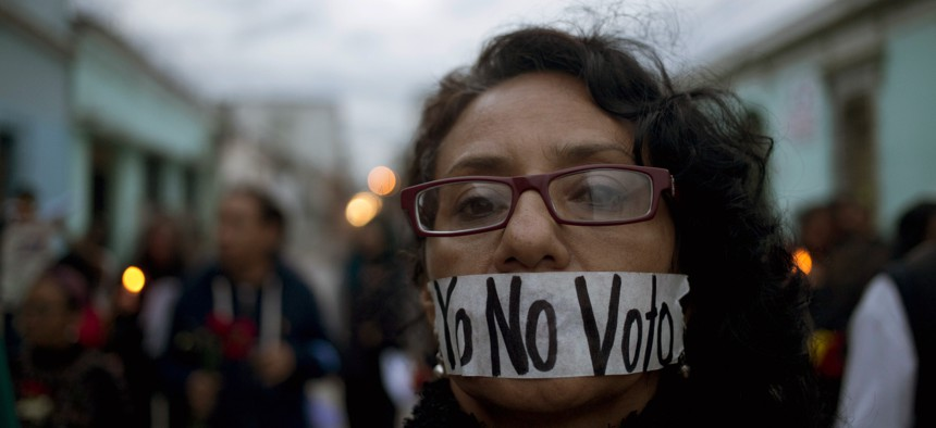 """A demonstrator covers her mouth with tape carrying the message Spanish: """"I'm not voting,"""" during a protest demanding election reform in Guatemala City, Saturday, Sept. 5, 2015, the day before general elections."""