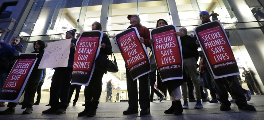 Protesters carry placards outside an Apple store in Boston on Feb. 23, 2016.