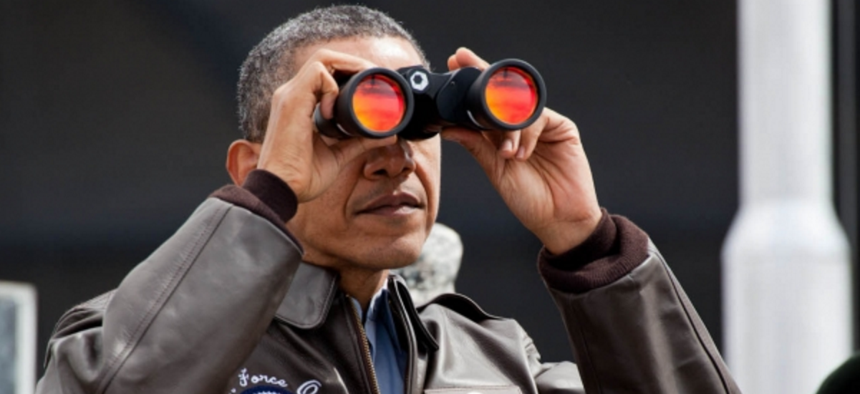 President Barack Obama uses binoculars to view the DMZ from Observation Post Ouellette at Camp Bonifas, Republic of Korea, March 25, 2012.