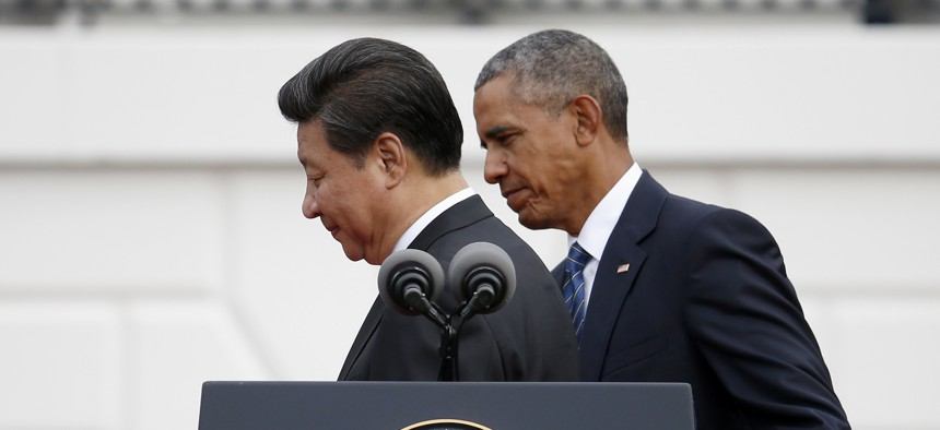 President Barack Obama guides Chinese President Xi Jinping off the podium at the conclusion of the official state arrival ceremony for the Chinese president, Friday, Sept. 25, 2015, on the South Lawn of the White House in Washington.
