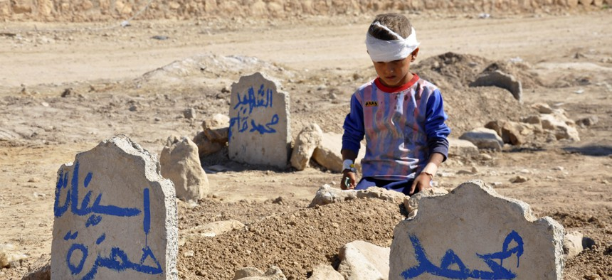 Ali Hamza, 8, sits at the graves of his brother, Mohammed, and sister Asinat, who were killed at their school when a suicide car bomb attack near Qabak elementary school in the Shiite Turkomen village of Qabak, just outside of in Tal Afar, Oct. 7, 2013.